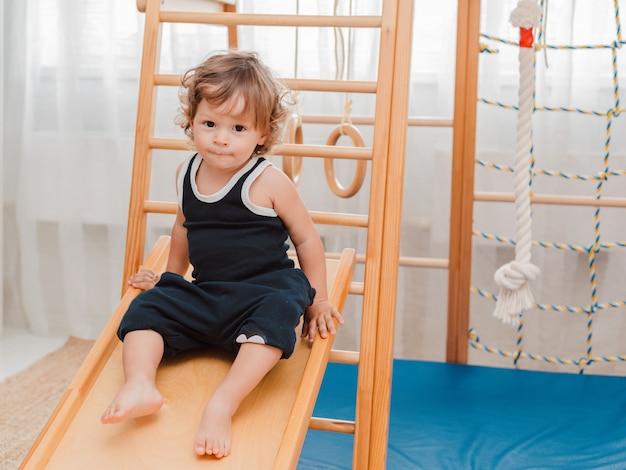 幼い1.5歳の子供は、家庭の子供の木製スポーツ施設に従事しています。 Premium写真