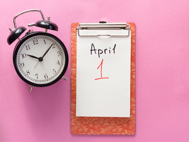 1 april fool's day, notebook, clock, pen. flat lay on pink background. Premium Photo