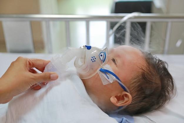 患者のベッドの上に1歳の男の子の吸い込みの男の子。 rsウイルス Premium写真