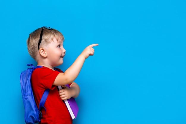 学校に戻る1年生のジュニアライフスタイル。赤いtシャツの小さな男の子。カバンと彼の指で指している本とメガネで微笑む少年のスタジオ写真の肖像画を間近します。 Premium写真