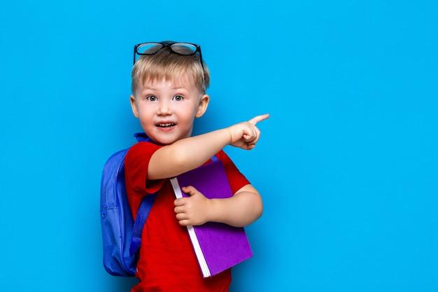 学校に戻る1年生のジュニアライフスタイル。赤いtシャツの小さな男の子。彼の指で示す、通学と本を持つメガネで微笑む少年のスタジオ写真の肖像画を間近します。 Premium写真