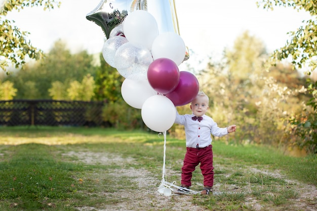 1 year old boy sitting on green grass outdoor playing with balloon. Premium Photo