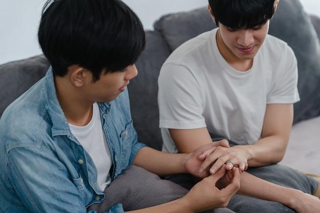 若いアジアの同性愛者のカップルが自宅で提案し、10代の韓国lgbtq男性の幸せな笑顔はロマンチックな時間を提案し、結婚の驚きは家のリビングルームで結婚指輪を着用します。 無料写真