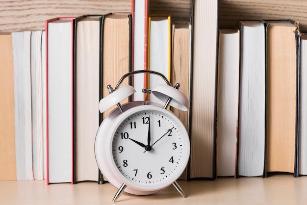 木製の机の上の本棚の前に10'o時計を示す白い目覚まし時計 無料写真
