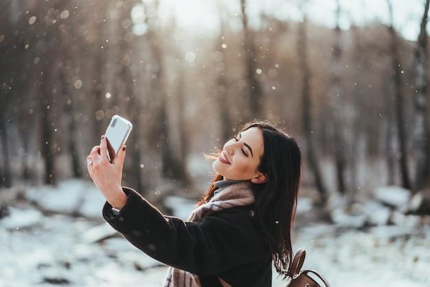 幸せな笑顔の10代の少女や冬の公園でスマートフォンでselfieを取る若い女性 無料写真