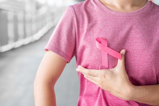 10月の乳がん啓発月間、人々の生活と病気をサポートするためのピンクのリボンが付いたピンクのtシャツの女性。医療、国際女性の日、世界がんの日コンセプト Premium写真