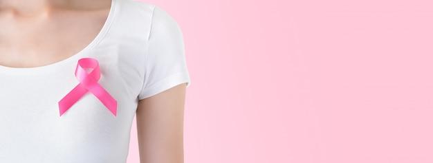 10月の乳がん啓発キャンペーンのシンボルをサポートする彼女の胸にピンクのリボンが付いた白いtシャツの女性 Premium写真