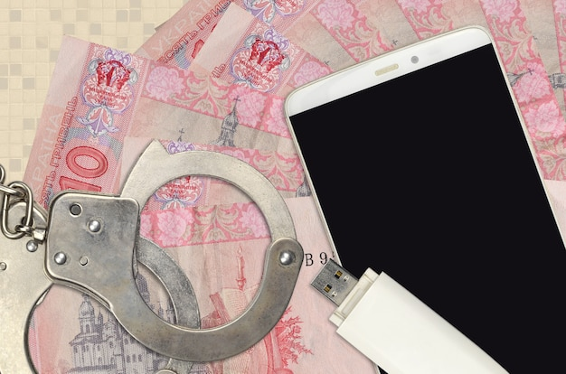 10 ukrainian hryvnias bills and smartphone with police handcuffs. concept of hackers phishing attacks, illegal scam or malware soft distribution Premium Photo