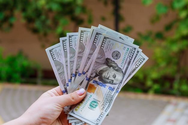 100 - долларовые купюры в руках женщины. считайте или тратьте деньги. Premium Фотографии