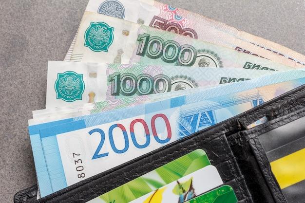 黒い革製の財布のクローズアップで1000、2000、5000ルーブルとクレジットカードの宗派の新しいロシアの紙幣 Premium写真