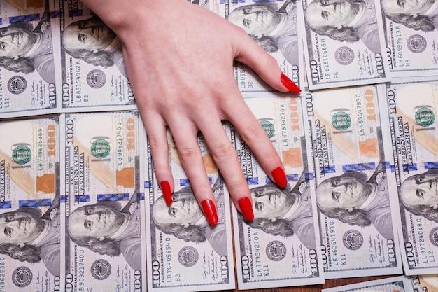お金、お金の欲、お金の背景、100ドル札のフロントサイドに横たわっているお金の上に横たわる赤い爪を持つ女性の手。ドルの背景 Premium写真