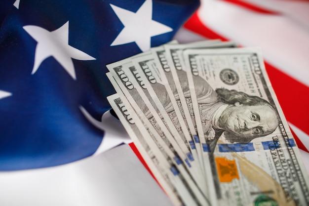 アメリカドルの現金。アメリカの旗の背景に100ドル紙幣のクローズアップ Premium写真