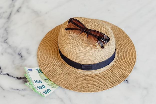 Шляпа от солнца с солнцезащитные очки и банкноты 100 сотых евро. концепция отдыха Premium Фотографии
