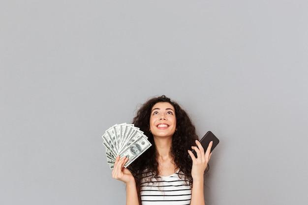 Симпатичная женщина в полосатой футболке держит веер 100 долларовых купюр и сотовый телефон в руках смотрит вверх, будучи благодарной, не может поверить в ее триумф Бесплатные Фотографии