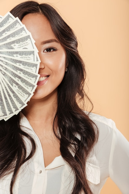 桃の背景に成功した実業家である100ドル札のファンと笑顔と彼女の顔の半分をカバーするアジアのブルネットの女性 無料写真