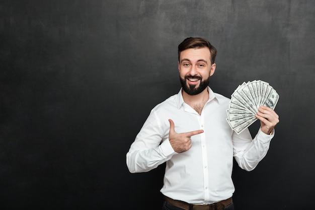 Портрет взрослого мужчины в белой рубашке позирует на камеру с веером 100 долларовых купюр в руке, будучи богатым и счастливым на темно-сером Бесплатные Фотографии