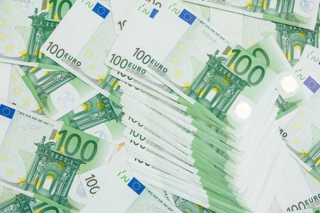 100ユーロの多くの紙幣、ヨーロッパの通貨の山 Premium写真