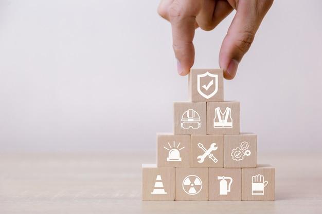 Поместите деревянные блоки на пирамиду. 100-процентная концепция безопасности труда. Premium Фотографии