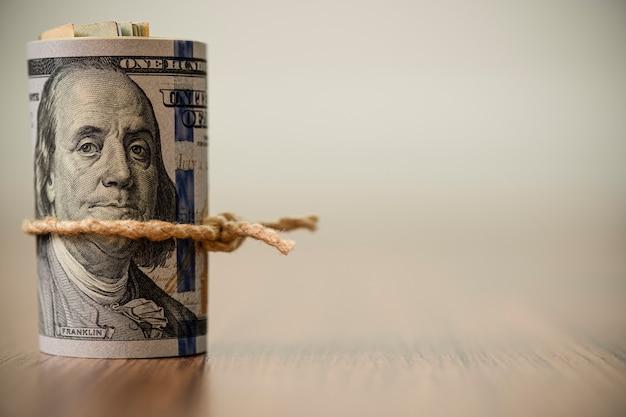 Макрос рулона 100 долларов сша банкноты на деревянных фоне и копией пространства Premium Фотографии