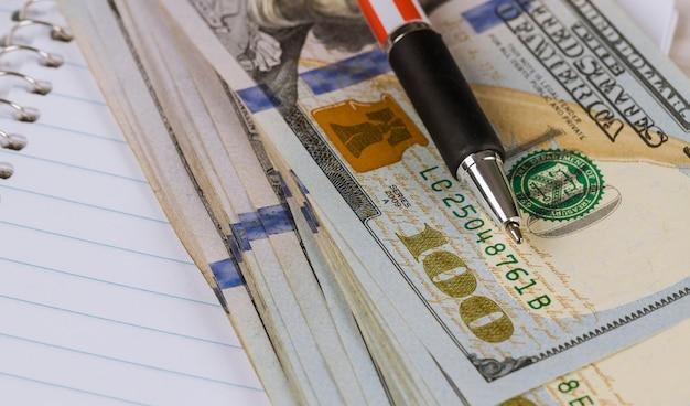 現金100ドル紙幣とペン Premium写真