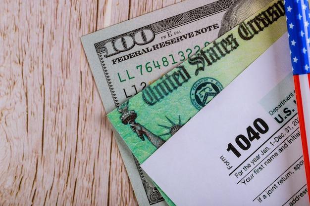 Стимул проверки экономической налоговой декларации и 100 долларовых банкнот валюты Premium Фотографии