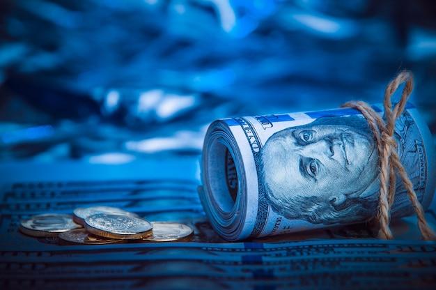 青い光の中で散在する100ドル紙幣の背景にコインとドルのロール。 Premium写真