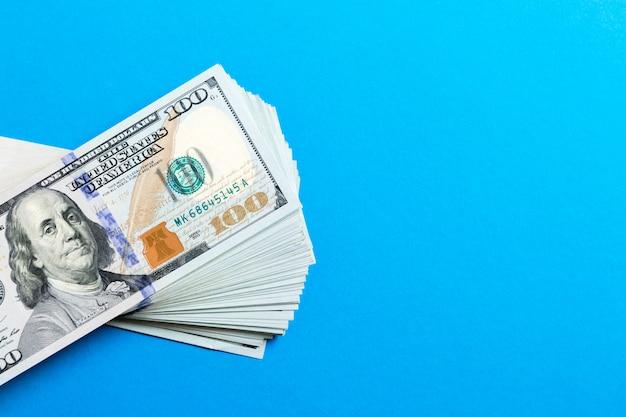 Стог банкнот 100 долларов на красочной предпосылке. вид сверху финансовой концепции с пустым пространством для вашего дизайна Premium Фотографии