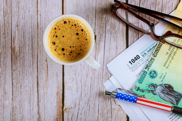 1040 tax forms top view with coffee cup and refund check, pencil with glasses Premium Photo