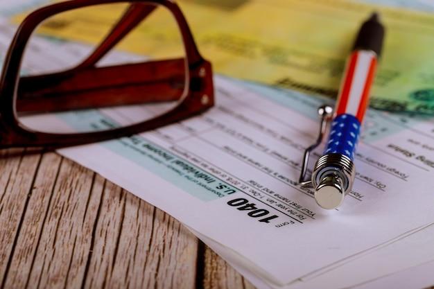 Налоговая форма 1040 с ручкой, очки с бухгалтерией, декларация о подоходном налоге Premium Фотографии