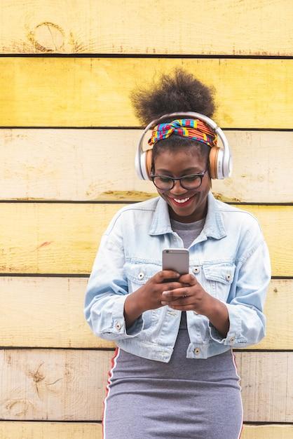 携帯電話を屋外で使うアフロアメリカンの10代の少女。 Premium写真