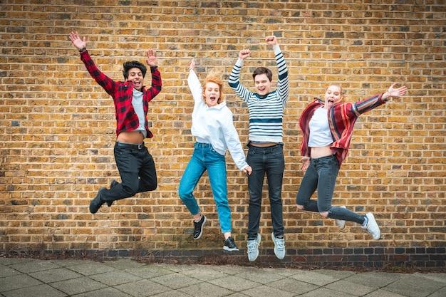 壁の前でジャンプ幸せな10代の友人 Premium写真