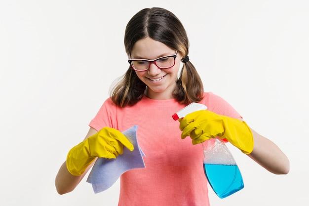 ぼろとスプレー洗剤で黄色い手袋の女の子10代。 Premium写真