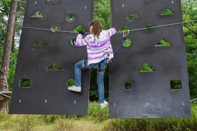 少女はハイワイヤーパークを登る冒険で10歳です Premium写真