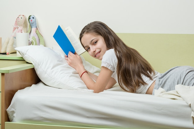 家で10代の少女は彼女の部屋のベッドで本を読みます Premium写真