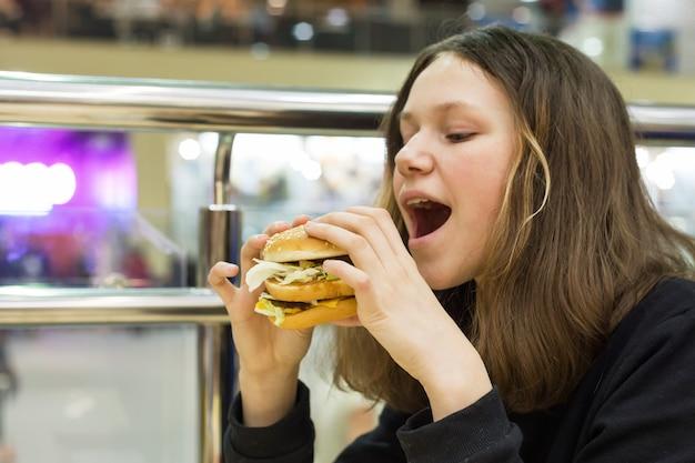 ハンバーガーを食べる10代の少女 Premium写真