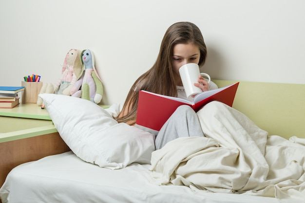 パジャマで10歳の十代の少女は本を読みます Premium写真