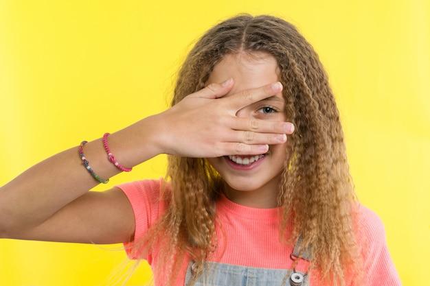 10代の少女の肖像画は、指でのぞき見します。 Premium写真