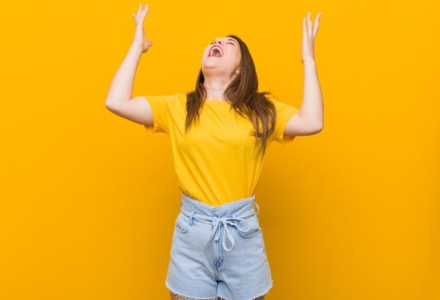 空に叫んで、見上げて、イライラした黄色のシャツを着た若い女性10代。 Premium写真