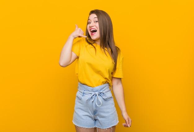 指で携帯電話の呼び出しジェスチャーを示す黄色のシャツを着ている若い女性10代。 Premium写真