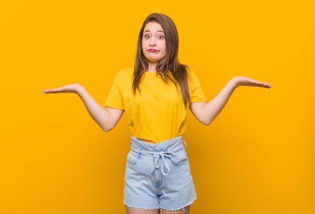 ジェスチャーを疑って肩を疑い、肩をすくめて黄色のシャツを着た若い女性10代。 Premium写真