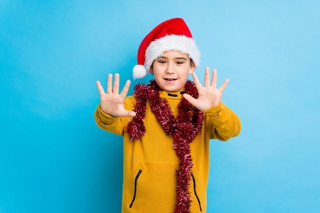 サンタの帽子をかぶってクリスマスの日を祝う少年は手で番号10を示します。 Premium写真