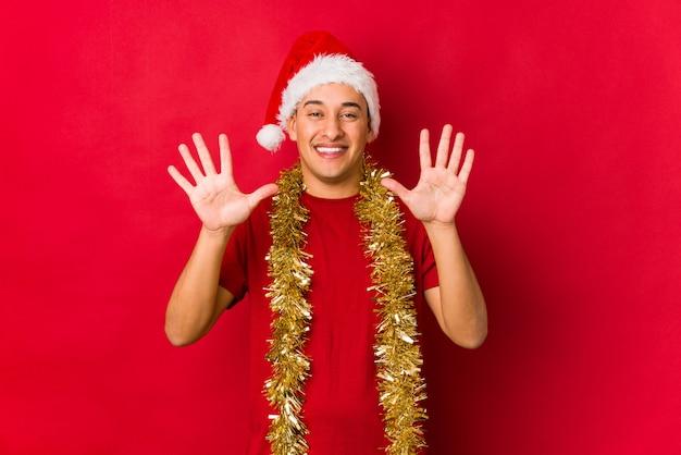 クリスマスの日に手で番号10を示す若い男。 Premium写真