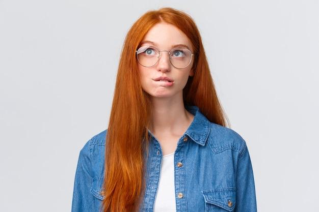 思慮深く、好奇心が強い赤毛の10代の少女の唇をかむと何かを計画として見上げる Premium写真