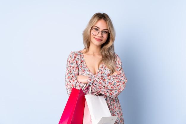 メガネと笑みを浮かべて青い壁に買い物袋を持つ10代のロシアの女の子 Premium写真