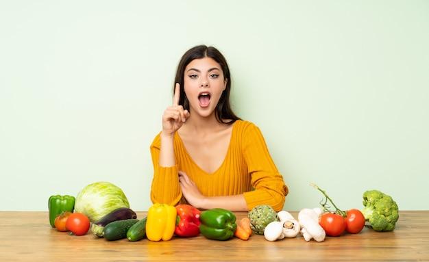 指を上向きにする考えを考えて多くの野菜と10代の女の子 Premium写真