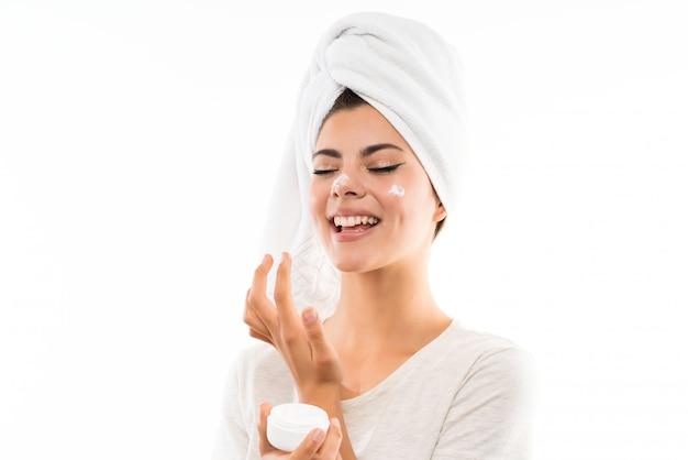 保湿剤で孤立した白で10代の女の子 Premium写真