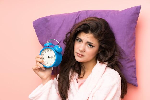 ピンクの背景の上のドレッシングガウンで10代の女の子とビンテージ時計を持って強調 Premium写真
