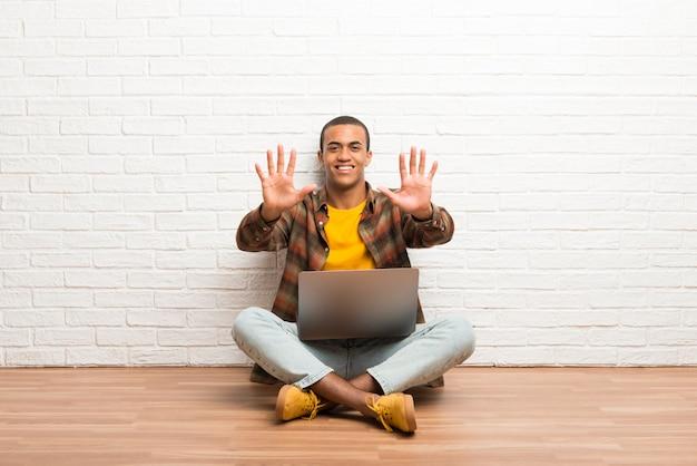 指で10を数える彼のラップトップで床に座っているアフリカ系アメリカ人の男 Premium写真