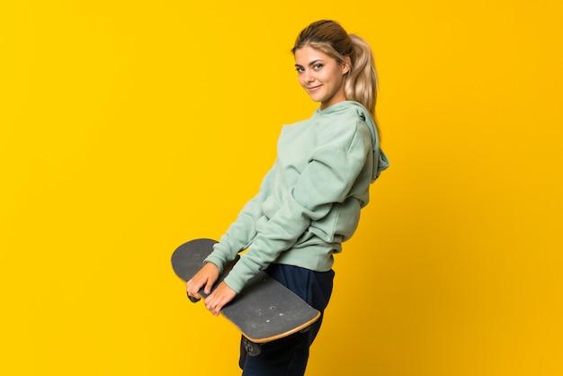 孤立した黄色の上の金髪の10代のスケーターの女の子 Premium写真