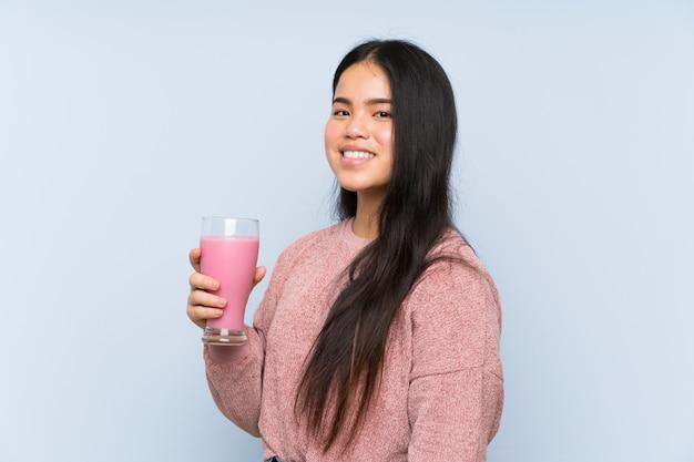 いちごのミルクセーキと若い10代のアジアの女の子 Premium写真